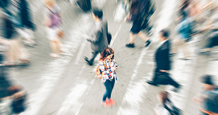 A women standing on a cross walk, looking at her phone, people walking past her are blurry