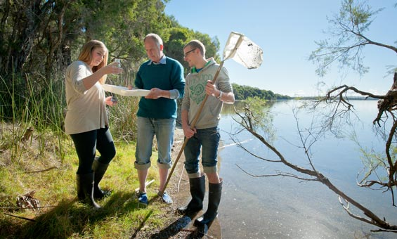 Three researchers observing samples by a lake