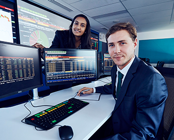 Two students in the SMART lab, computer monitors with financial data displayed.