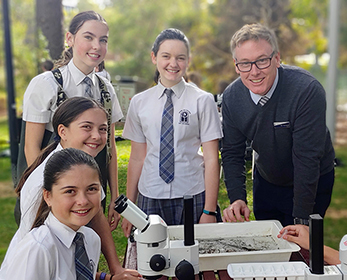 Mater Dei College students and teacher conducting a science experiment..