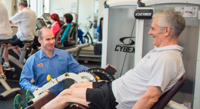 Man helping another man on leg exercise equipment