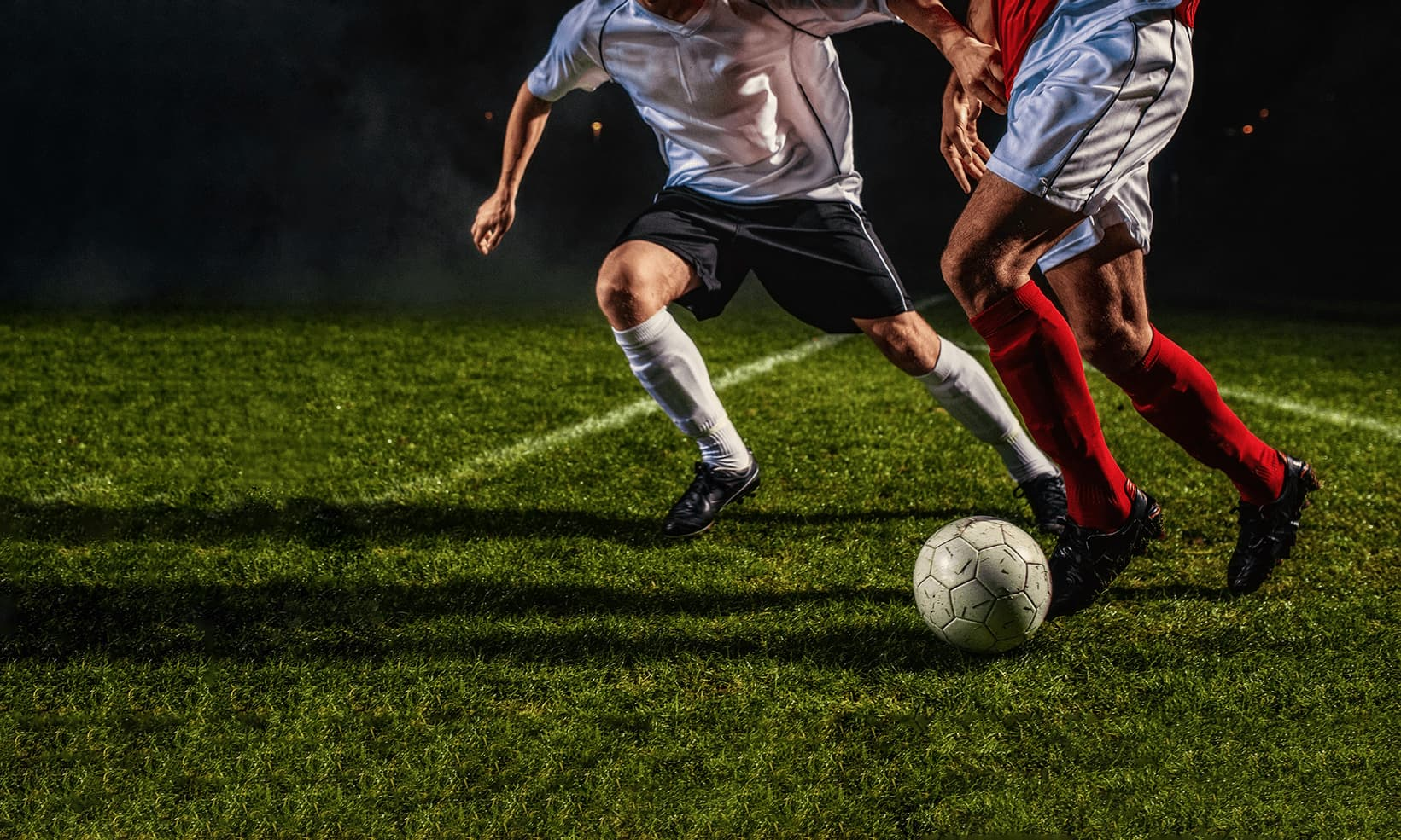 Two soccer players from opposing teams playing on grass field, at night, lit by floodlights