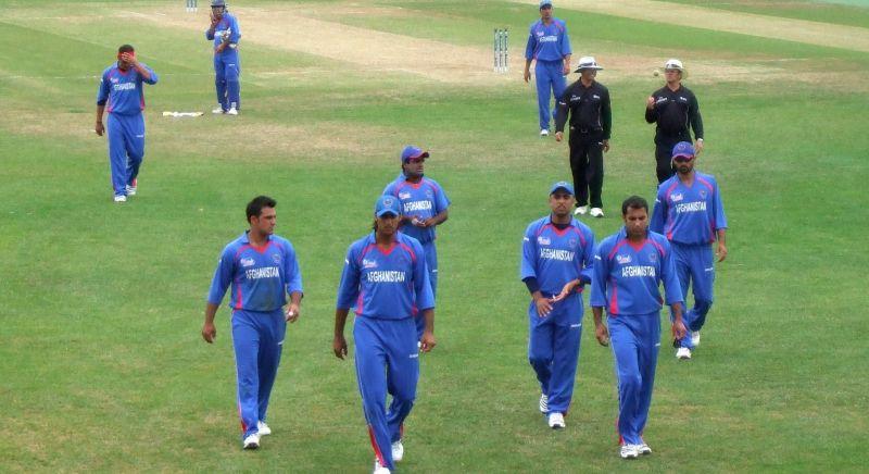 Men walking off cricket field