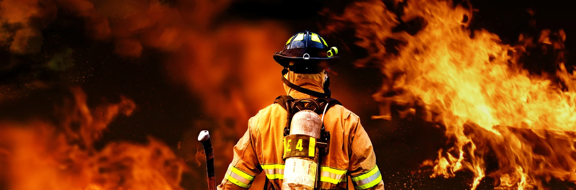 Firefighter standing in front of a wall of flames