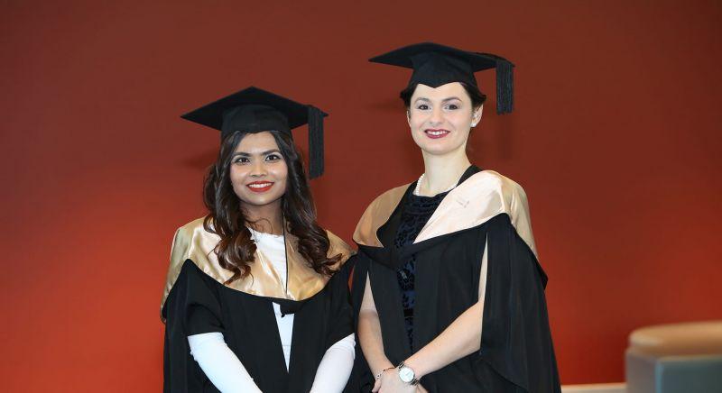 ECU students Maisha Zuhair and Andra Dinu standing together in their graduation regalia