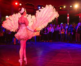 A dancer wearing feathers and sequins stands stage left looking out into an amphitheatre.