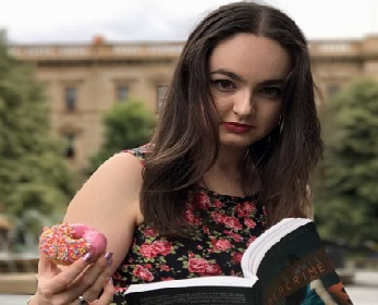 Lecturer Brianna Jane O'Shea holding a book in left hand and a donut in the right