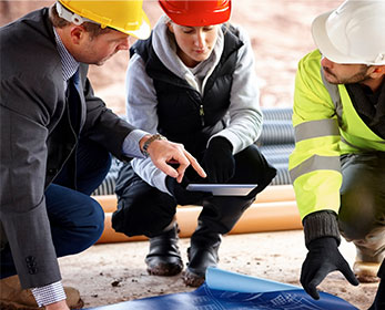 Professional workers looking at the iPad and blueprints on a work site..
