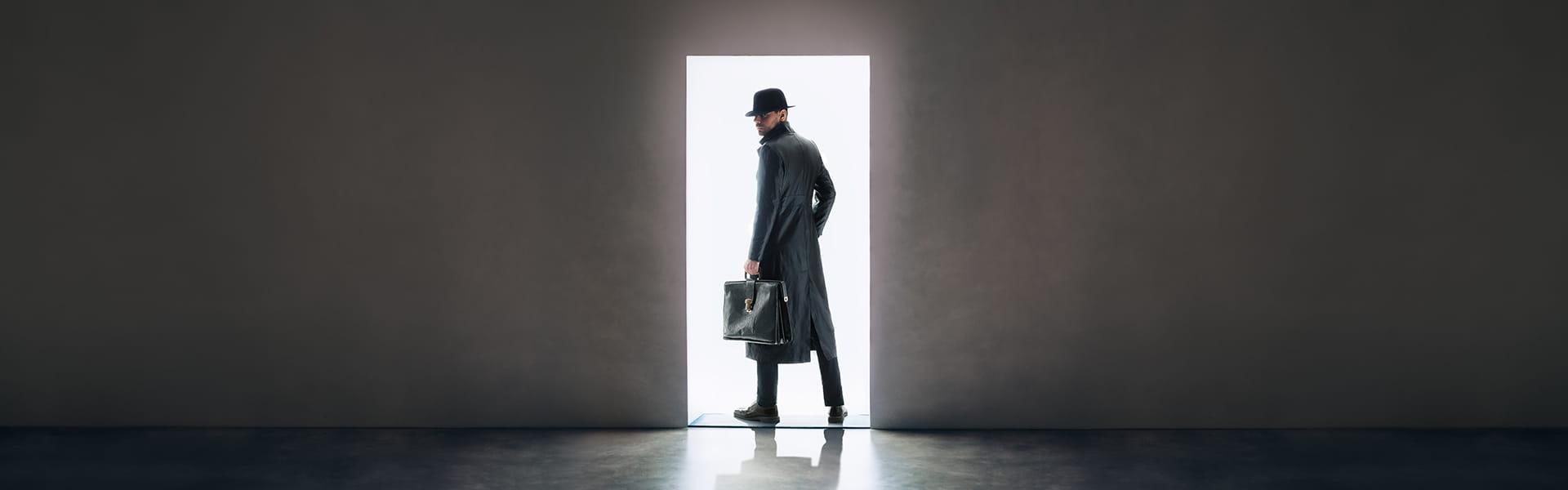 Man silhouette in hat and raincoat standing in the light of opening door in dark room