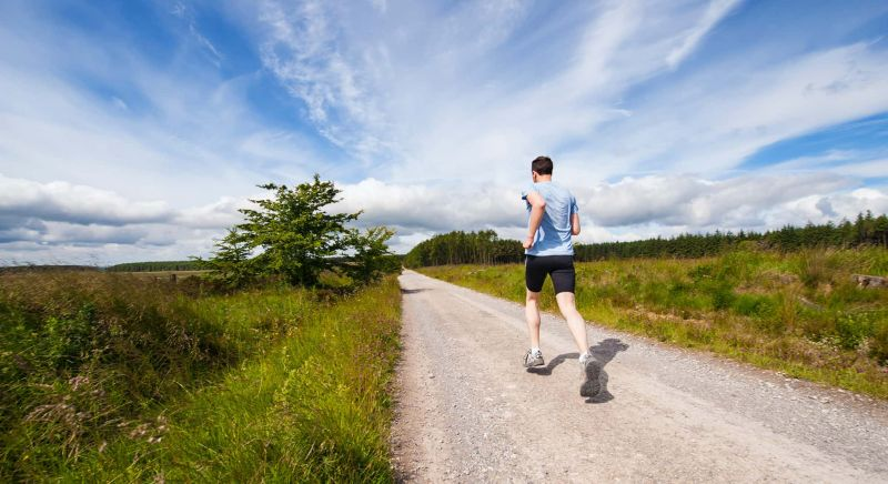 Image of man running on an unsealed country road.